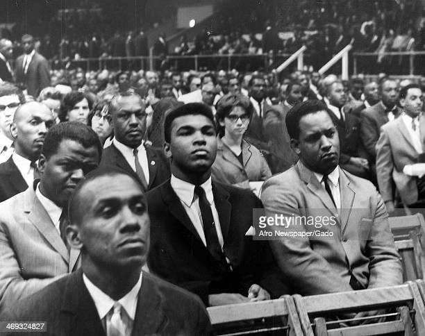 Cassius Clay heavyweight boxing contender listens to Elijah Muhammad the leader of the group Nation of Islam speaking at a rally prior to Elijah...
