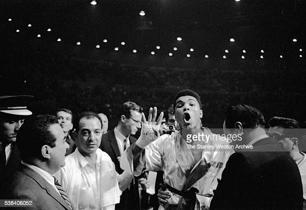 Cassius Clay puts up his four fingers after winning the bout to signify his win which he predicted stating that he would knock out Archie Moore in...