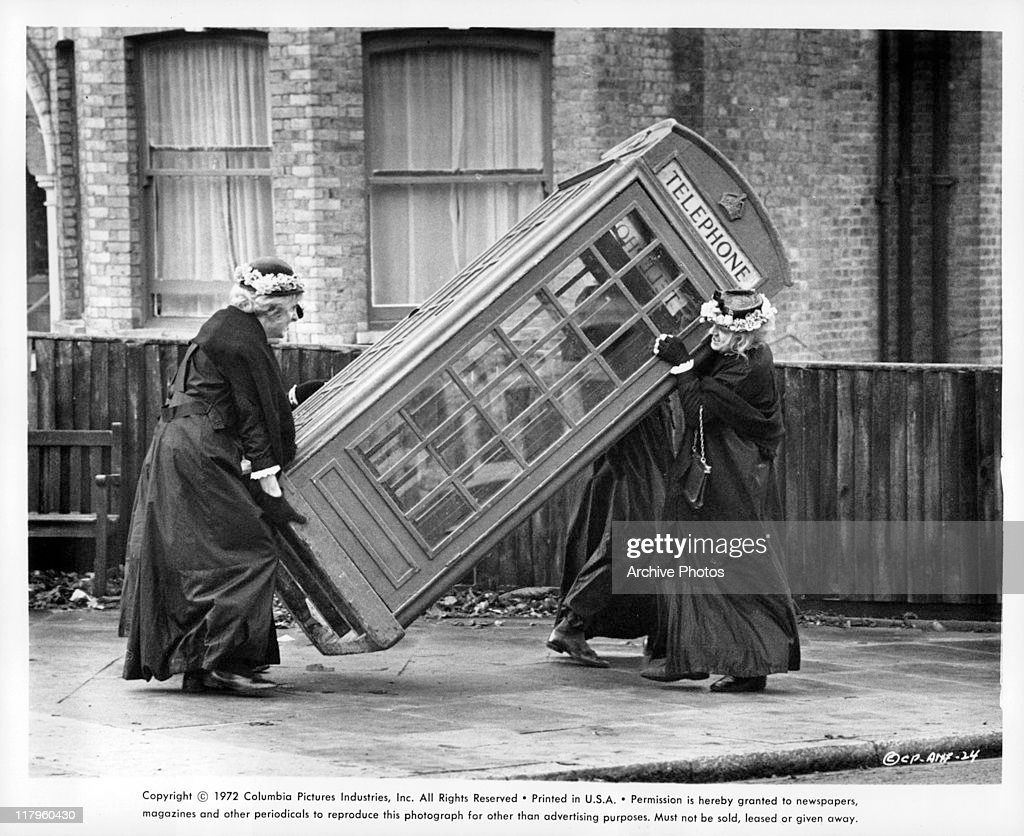 Cast dressed as old women lifting a telephone booth in a Hell's Grannies scene from the film 'And Now for Something Completely Different', 1972.
