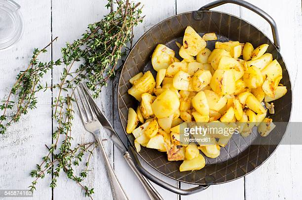 Cast iron frying pan of fried potatoes, thyme and cutlery on wood