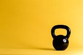 Cast iron kettlebell on a yellow background