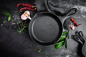 cast iron pan and spices on black metal culinary background