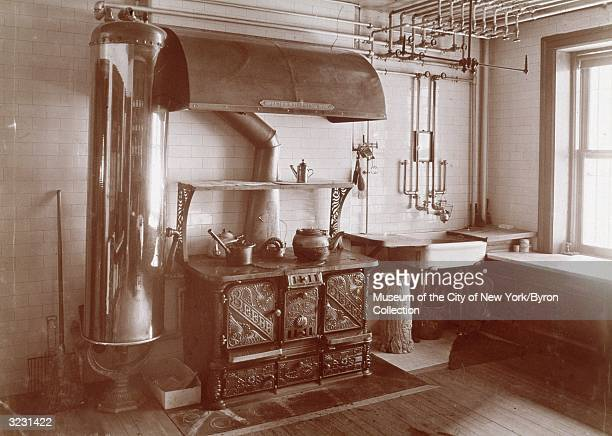 A cast iron stove and a water tank in the American Victorianstyle kitchen of the home of the Hon and Mrs Theodore Sutro 320 West 102nd Street New...