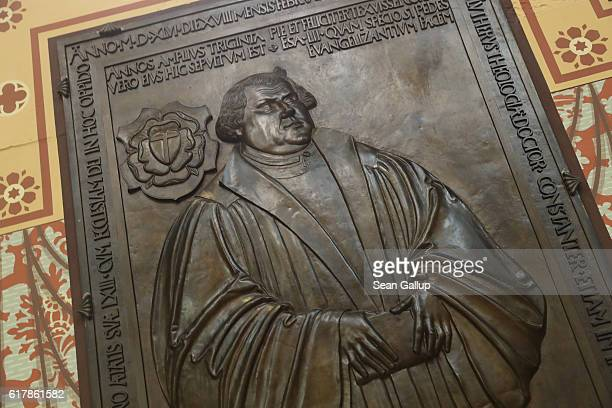 A cast metal relief showing Martin Luther hangs in the wall close to his tomb in the Schlosskirche church which is the same church where in 1517...