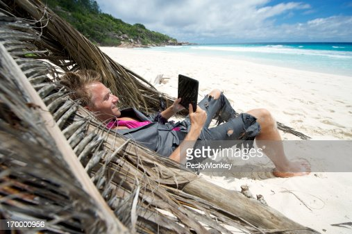 Castaway Businessman Relaxes on Beach with Tablet Computer