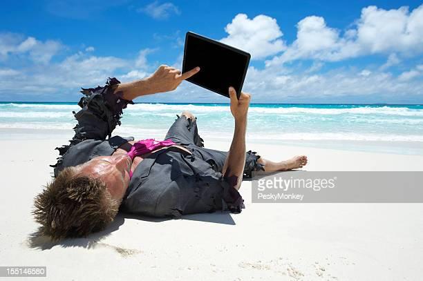 Castaway Businessman Using Tablet Computer on Beach