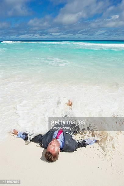 Naufrago Uomo d'affari lavaggi a terra in onda sulla spiaggia tropicale