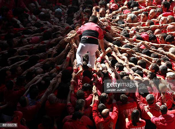 A casteller of the Colla Jove Xiquets de Tarragona 'colle' climbs up as the construction of a human tower begins during the 22nd Tarragona Castells...