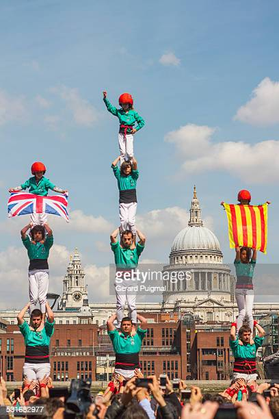 Castellers doing three human towers with St Paul's Cathedral in the background in London They are holding the flag of United Kingdom and the...