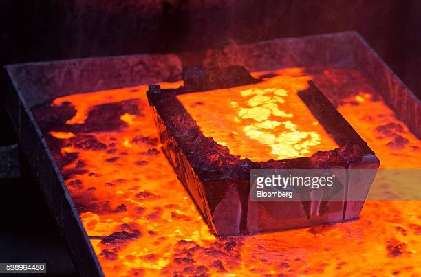 A casting mold filled with molten gold sits above a melting vat during the manufacture of gold ingots at the Suzdal gold mine operated by Nordgold NV...