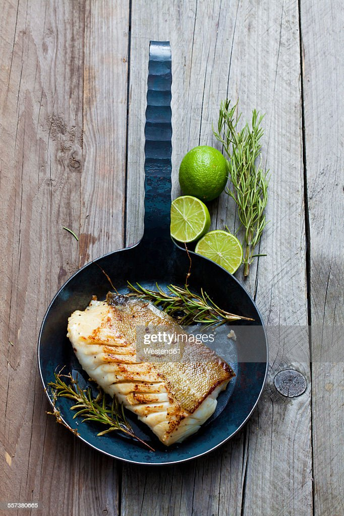 Cast-iron frying pan with piece of fried Norwegian codfish and twigs of rosmary