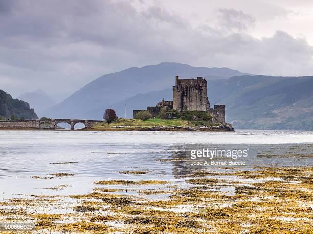 Castle and old bridge into a lake in Scotland