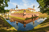 Nesvizh, Belarus - July 9, 2016: Stone building with towers, battlements and ramparts, surrounded by a moat filled with water. Nesvizh Palace - palace and castle complex. The castle was the ancestral