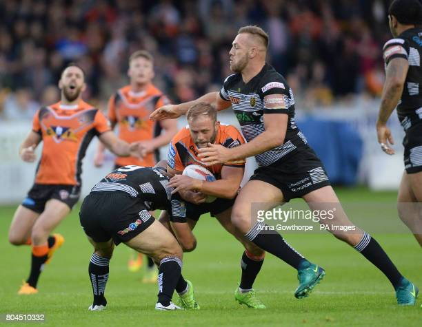 Castleford Tigers' Paul McShane is tackled by Hull FC's Danny Houghton and Liam Watts during the Betfred Super League match at the MendAHose Jungle...
