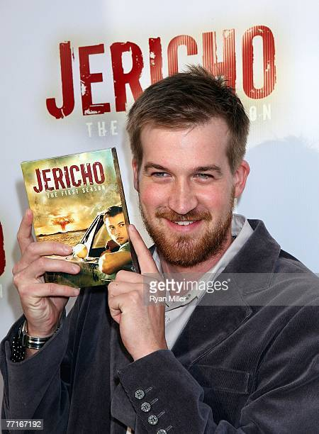 Castmember Kenneth Mitchell poses with a copy of the 'Jericho' DVD as he arrives for the CBS DVD release of 'Jericho The First Season' at the new...