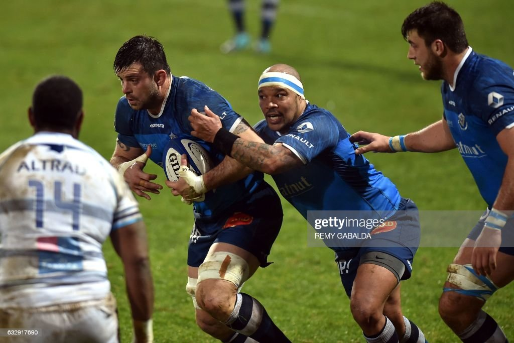 Castres' captain Capo Ortega (2nd L), flanked by Castres' South African prop Jody Jenneker (C), runs with the ball during the French Top 14 rugby union match between Castres and Montpellier, at the Pierre Antoine stadium in Castres southern France, on January 28, 2017. /