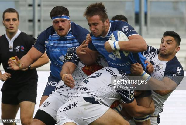 Castres' French flanker Anthony Jelonch is tackled by agen's hooker Facundo Bosch during the French Top 14 rugby union match between Castres and Agen...