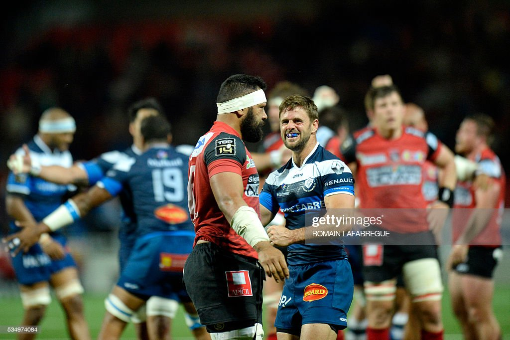 Castres' French scrumhalf Rory Kockott (R) smiles at Oyonnax' Tongan flanker Viliami Ma'afu (L) after the French Top 14 rugby union match between Oyonnax (USO) and Castres (CO) on May 28, 2016 at the Charles-Mathon stadium in Oyonnax, central eastern France. Castres won 25-20. / AFP / ROMAIN