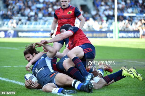 Castres' winger Taylor Paris is tackled by Munster's players during this Champions Cup rugby Union match between Castres Olympique Rugby and Munster...