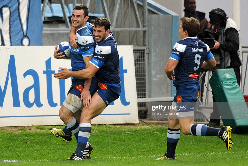 Castres's fullback Geoffrey Palis (L) celebrates with Castres's center Remi Lamerat after scoring the first try during the French Top 14 Rugby Union match Castres vs Pau at the Pierre Antoine Stadium in Castres, southern France on April 30, 2016.