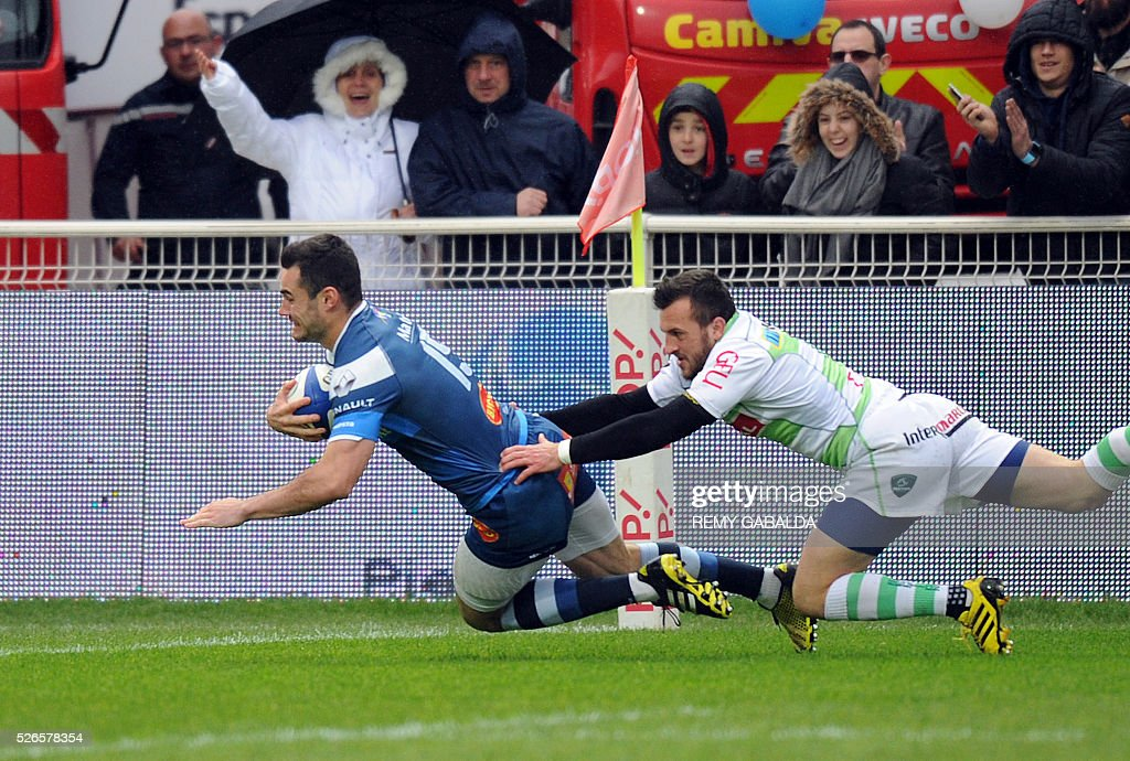 Castres's fullback Geoffrey Palis (L) scores the first try during the French Top 14 Rugby Union match Castres vs Pau at the Pierre Antoine Stadium in Castres, southern France on April 30, 2016.