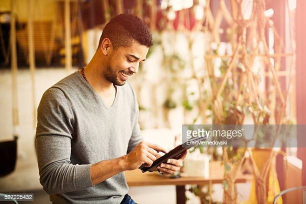 Casual African American businessman surfing the net on  tablet .
