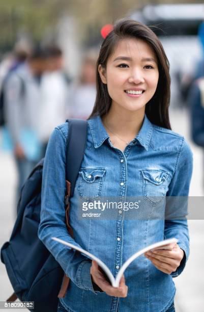 野外を歩いているカジュアルなアジア学生
