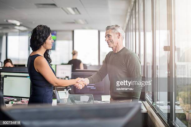 Casual business people shaking hands in the office