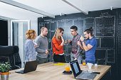 Creative agency concept - casual business people working together with computer in office