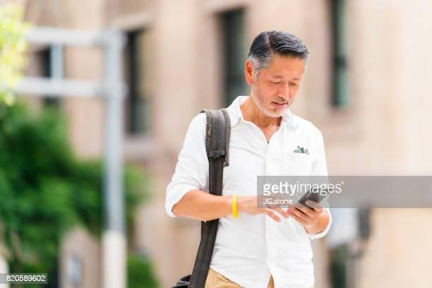 ビジネスカジュアル上級アジアふぐ男彼の携帯電話をチェック