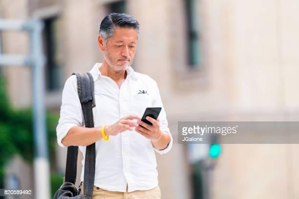 ビジネスカジュアル上級アジア男は彼の携帯電話をチェック