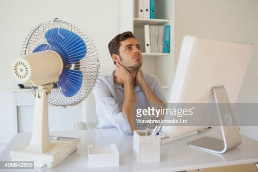 Casual businessman sitting at desk with electric fan : Foto de stock