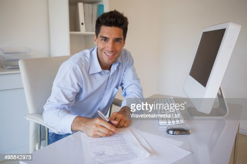 Casual businessman sitting at desk writing : Stock Photo