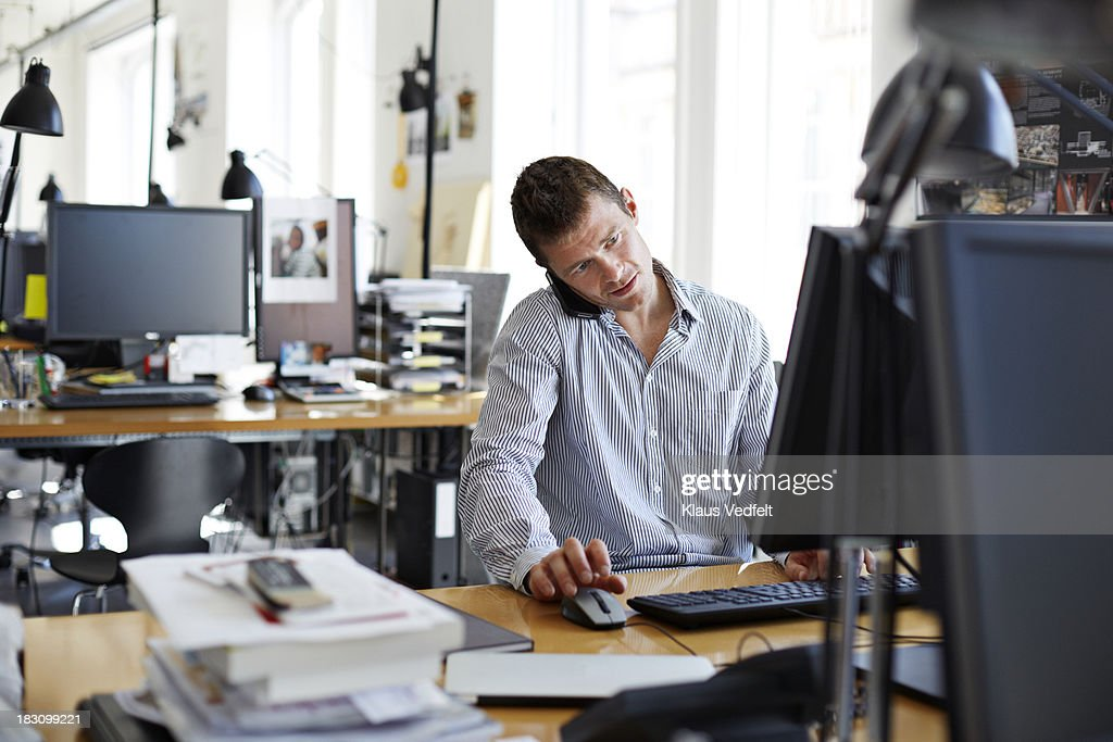 Casual businessman talking on phone & using mouse : Stock Photo