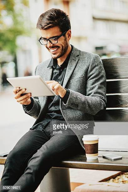 Casual businessman with digital tablet outdoors