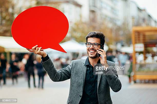 Casual businessman with phone and red speech bubble outdoors