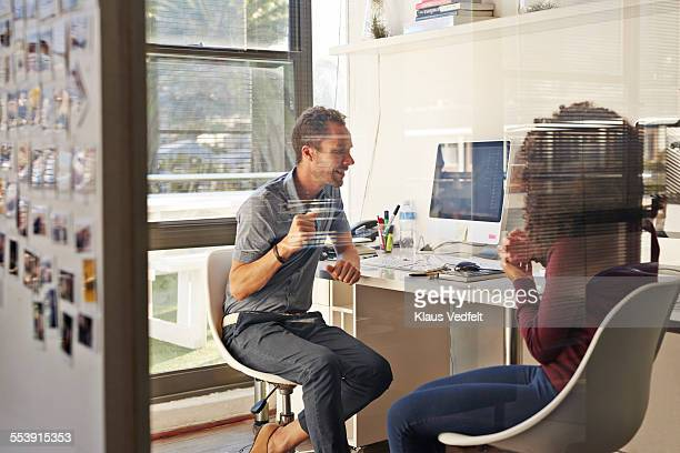 Casual businesspeople talking at their desk