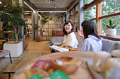 two businesswomen talking with smile at cafe; an image related to casual business, everyday small business arrangement, active woman in business, remote work, freelance work and so on