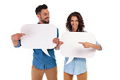 happy young casual couple holding speech bubbles pointing to each other on white background
