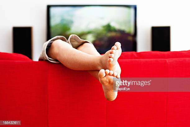 Casual cross-legged boy plays on red couch