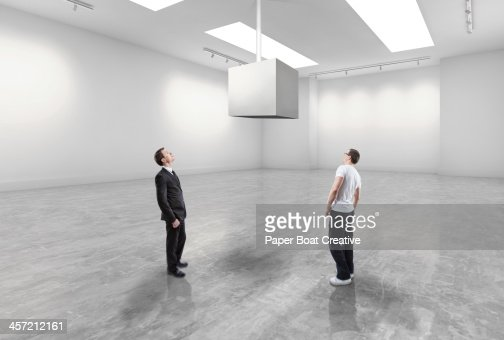 Casual man and business man looking at blank cube