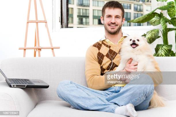 Casual Man at Home with Laptop Computer & Pomeranian