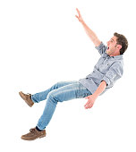 Casual man falling and looking worried  - isolated over a white background