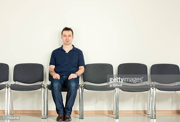 Legerer Mann sitzt auf Sesselreihe