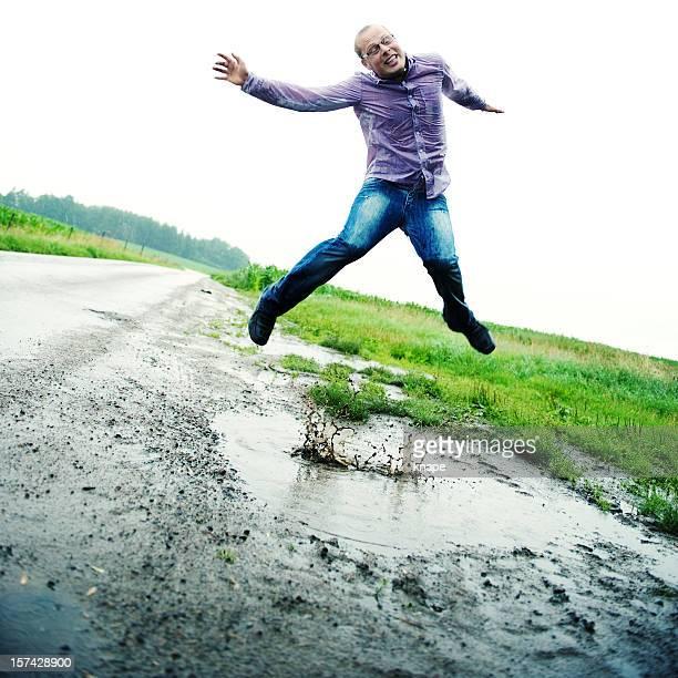 Legerer Mann Sprung in eine Pfütze mit Schlamm