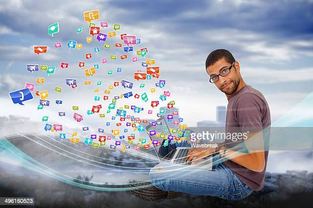 Casual man using laptop with app icons
