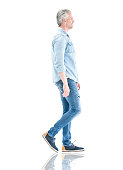 Casual adult man in denim clothes walking to the side - isolated over a white background