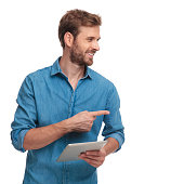casual man with tablet recommends something to side on white background