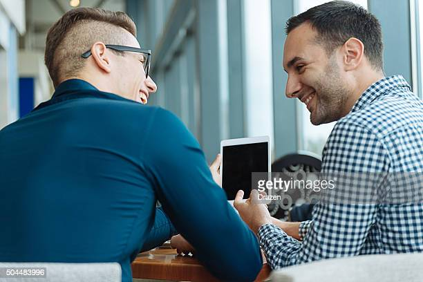 Casual men using digital tablet for communication and social networking