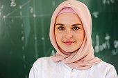 Arabic Muslim teenage student inside the high school classroom posing on board